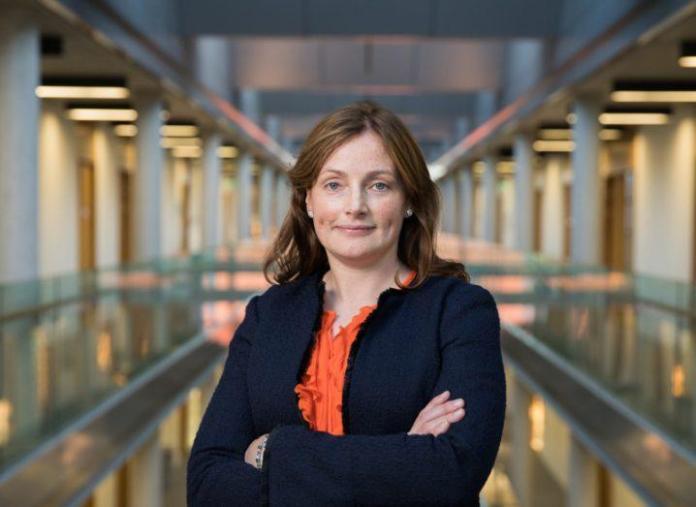 Femme aux cheveux bruns vêtue d'un haut orange et d'un blazer noir, les bras croisés, debout dans un couloir.