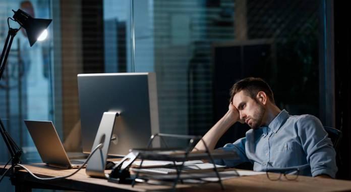 Homme décontracté à la recherche de fatigue alors qu'il travaillait avec l'ordinateur au bureau sombre seul.