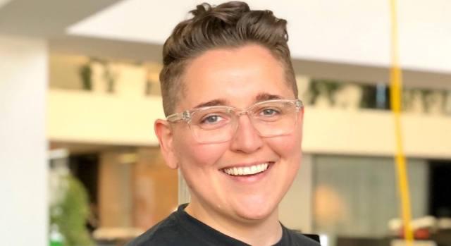 Une photo d'une jeune femme souriante aux cheveux courts et des lunettes. Elle travaille chez Spotify.