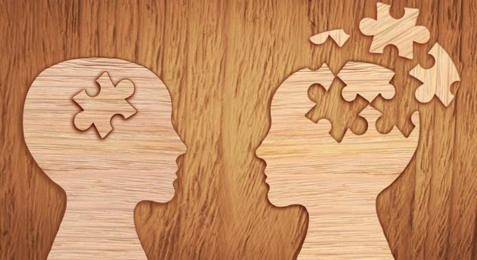 Une surface en bois avec deux têtes en bois se faisant face. L'un d'eux a cassé des morceaux de puzzle montrant une mauvaise santé mentale.