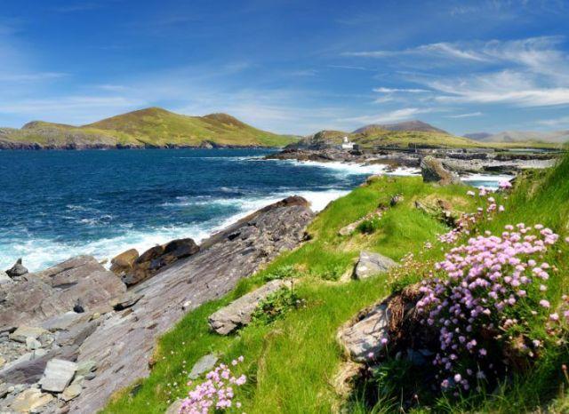Vue imprenable sur l'île Valentia dans le Kerry, avec de l'herbe verte, des rochers et des vagues dans la mer d'un bleu profond.