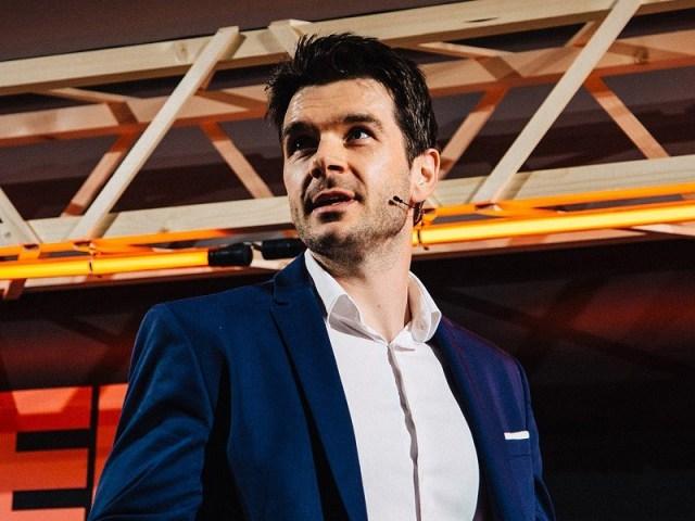 Aid: Le co-fondateur de Tech, Niall Dennehy, s'exprimant sur scène dans un blazer bleu et une chemise blanche.