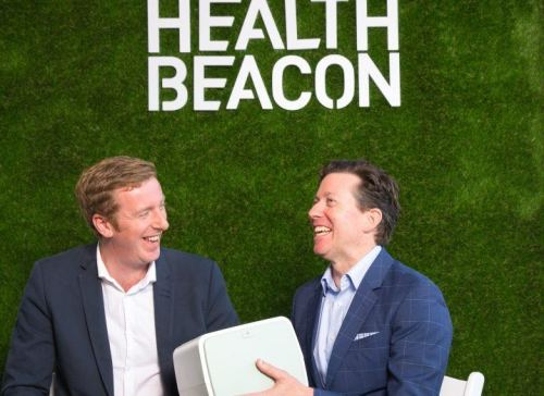 Two men in dark jackets sit before a green wall holding a white medical device.