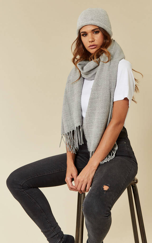Model wears light great wooly hat and scarf set with white t-shirt and grey jeans