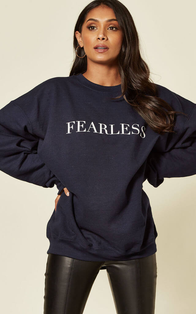 Model wears a navy sweatshirt with white fearless slogan with black jeans