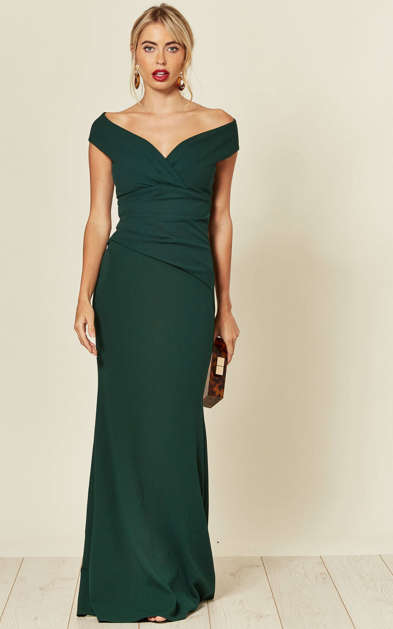 Model wears a maxi length dark green dress with fishtail hem