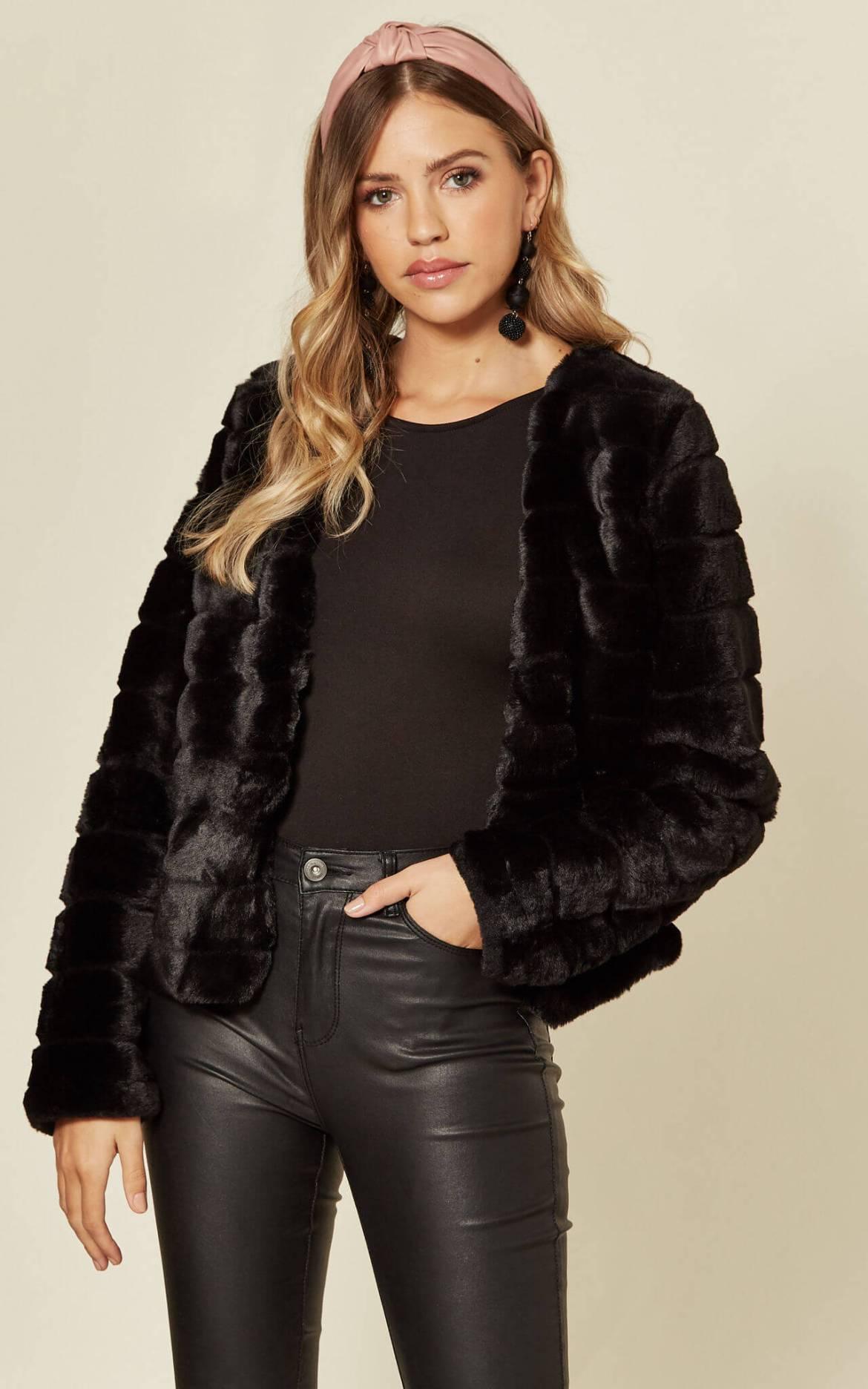 Model wears a collarless black faux fur coat