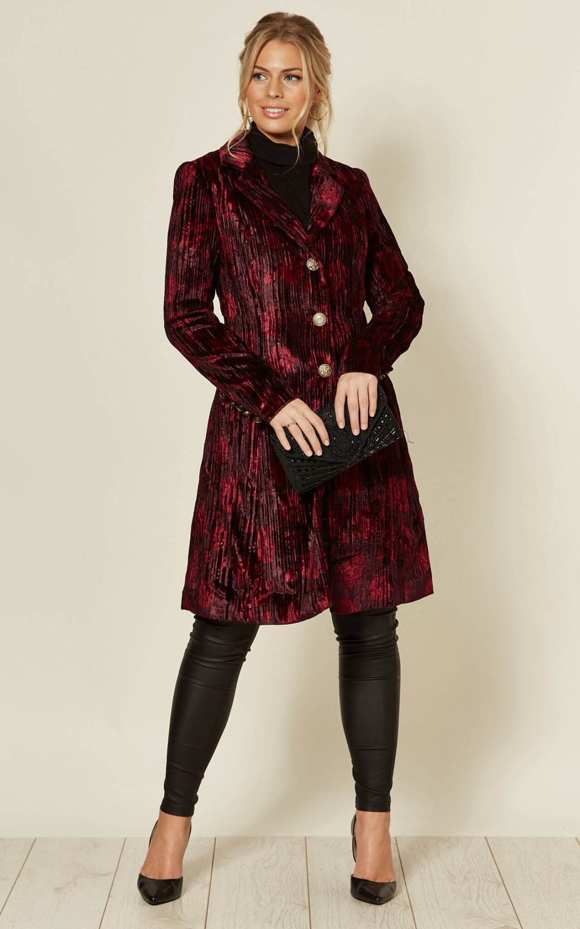 Model wears red crushed velvet coat in floral style print