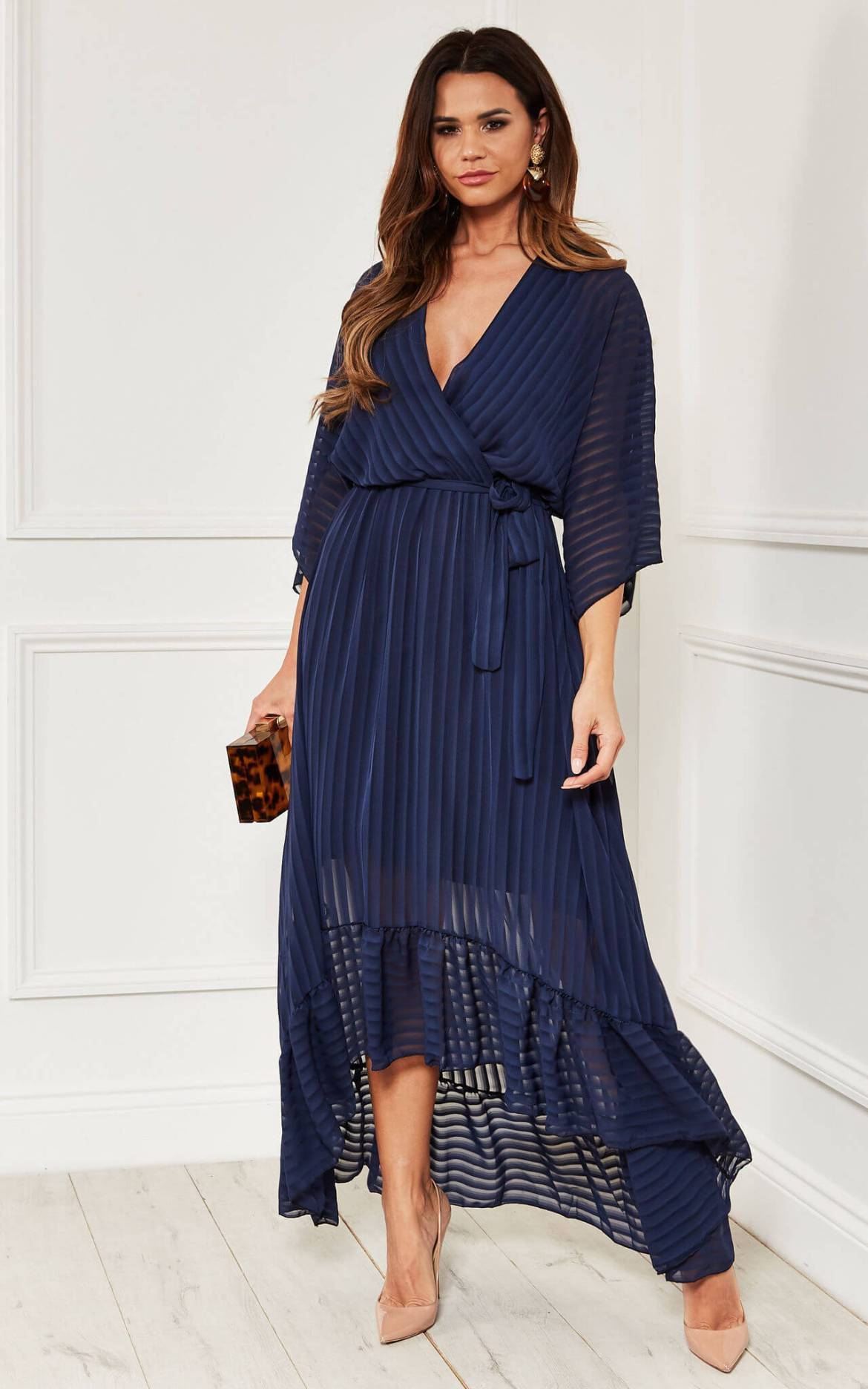 Model wears navy plunge maxi dress with tie side and frill hem