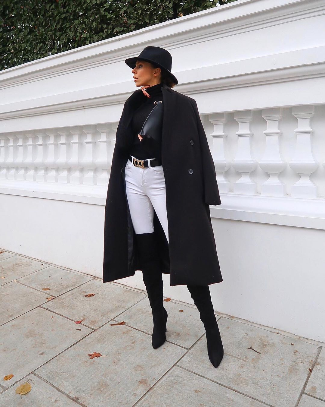 Model wears a black coat, knee high boots, hat and white jeans on London street