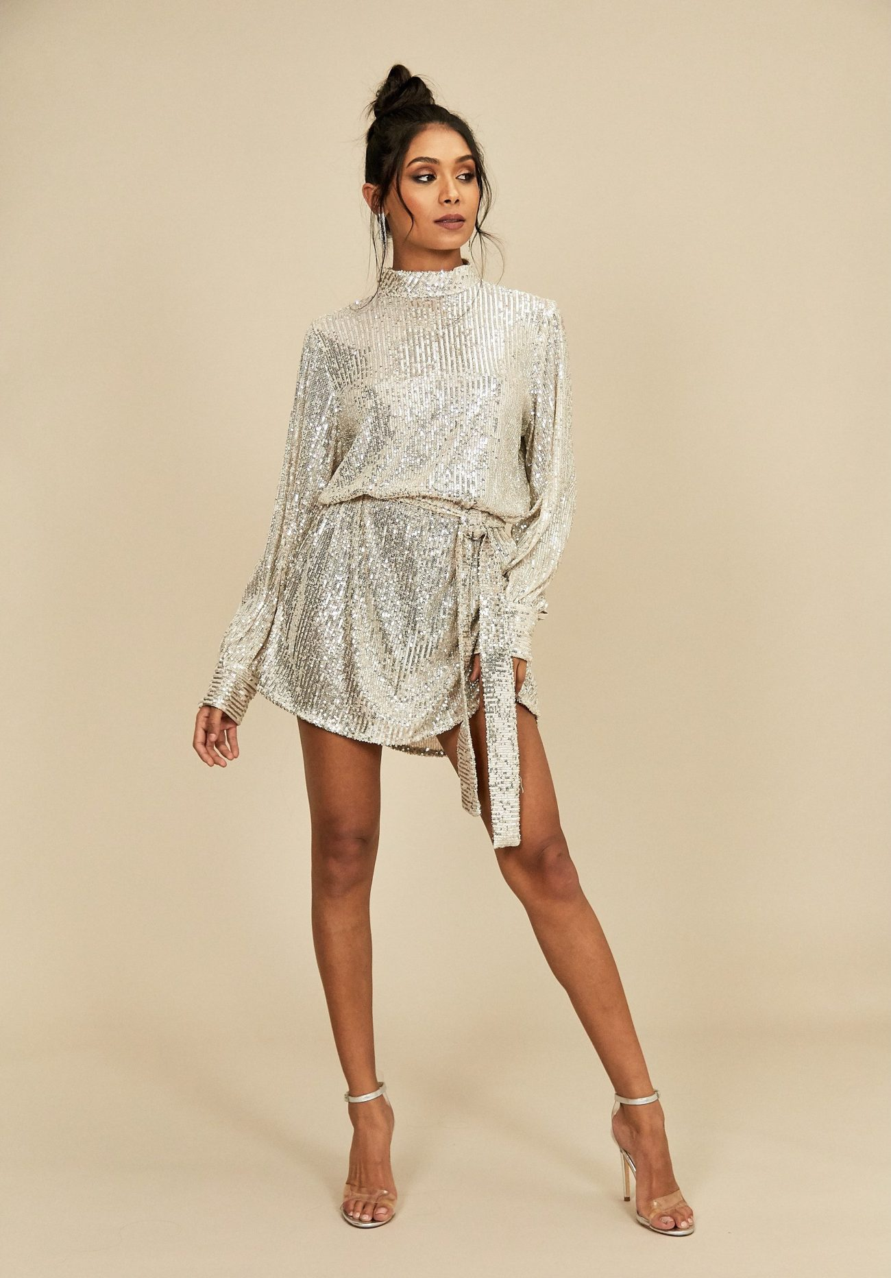 Model wears silver sequin mini dress with high neck and tie waist