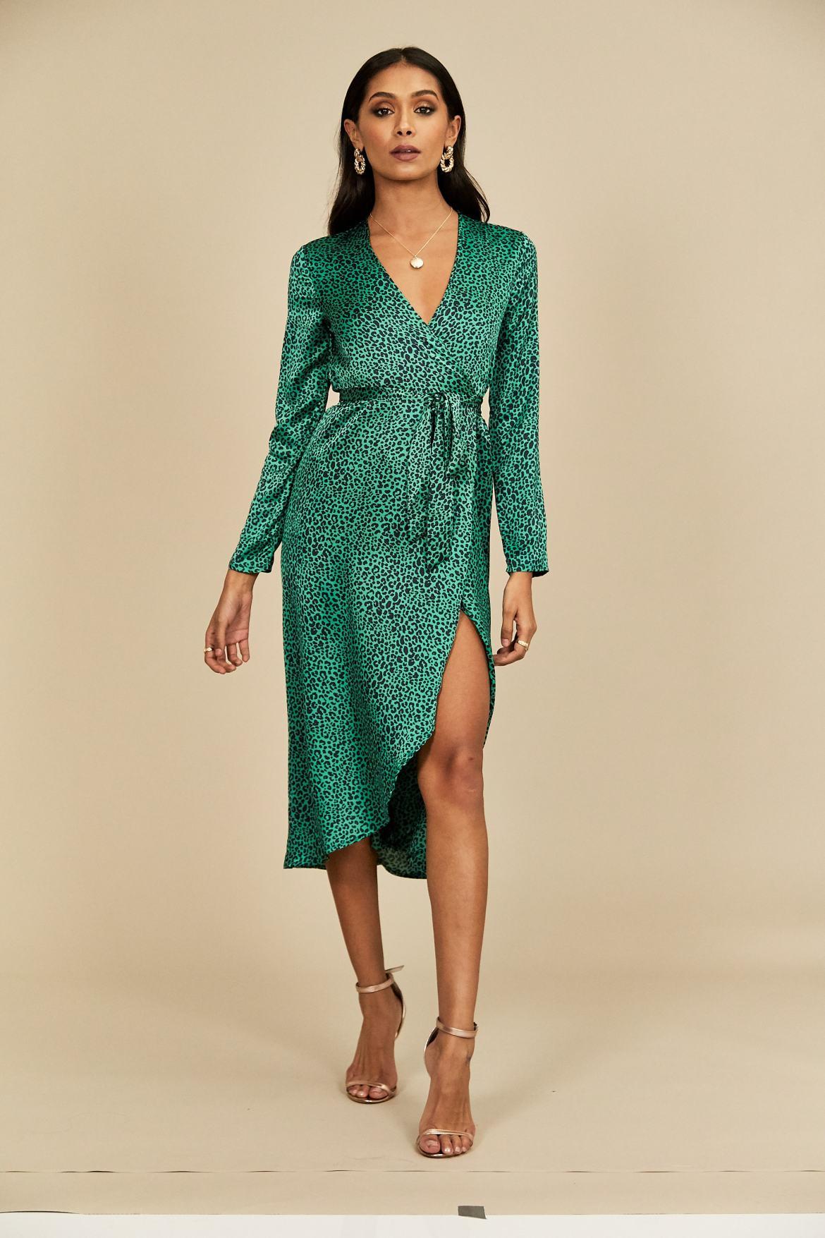 Model wears a green satin wrap midi dress with animal print