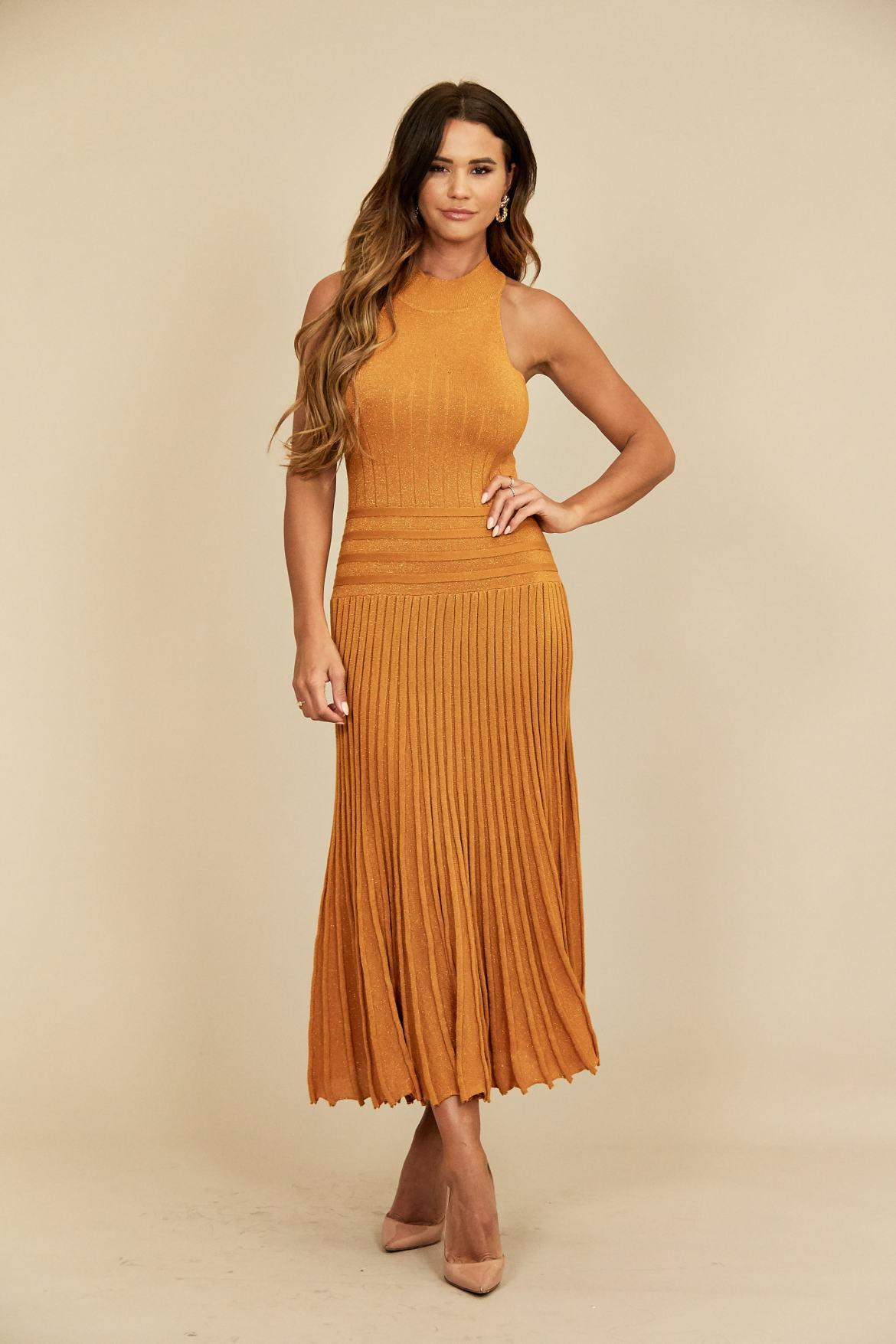 Model wears gold metallic high neck midi dress with pleated skirt