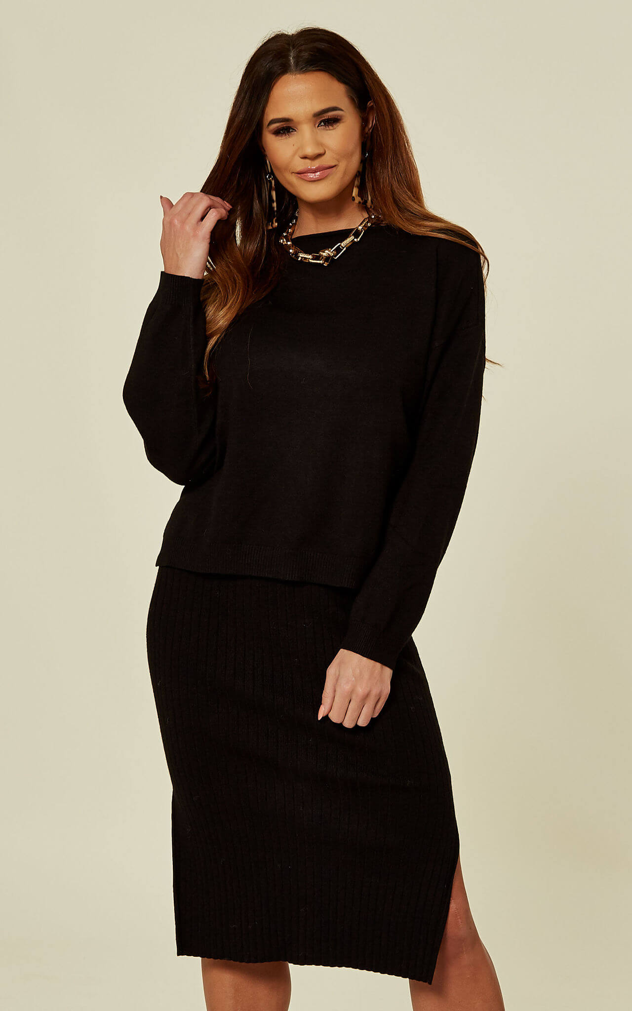 Model wears a knitted black dress and jumper set