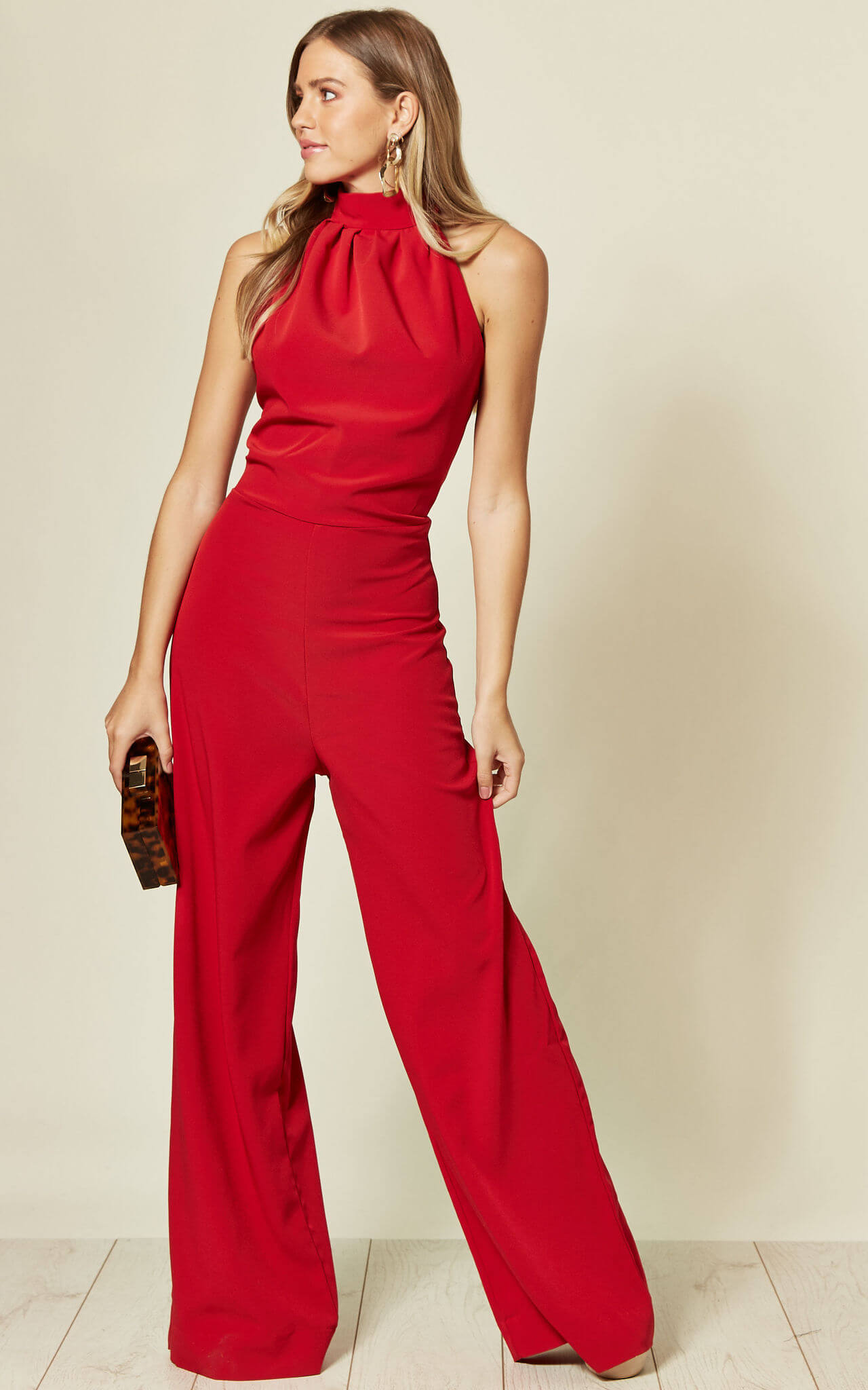 Model wears a high neck full length red jumpsuit with wide legs