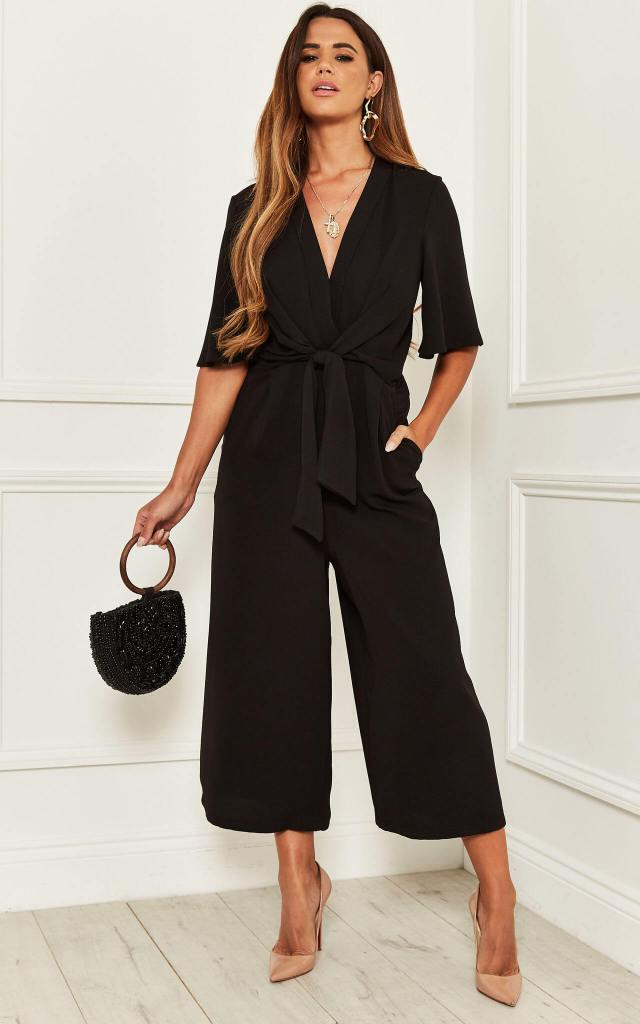Model wears black knot front jumpsuit with wide legs and black beaded bag