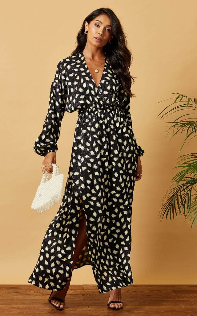 Model wears a ruffled maxi batwing dress in black and white