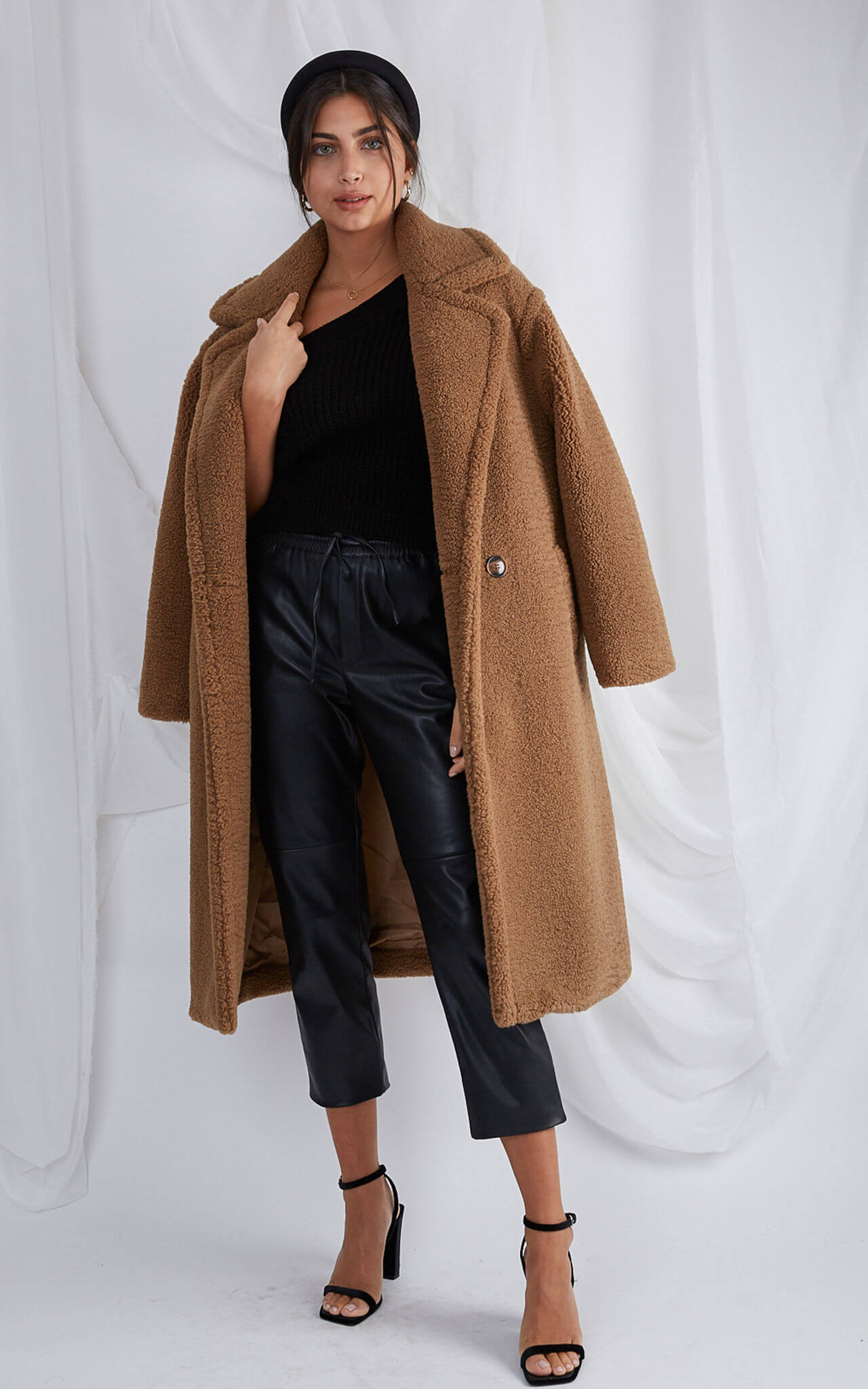 Model wears brown teddy coat over shoulders with black top and jeans
