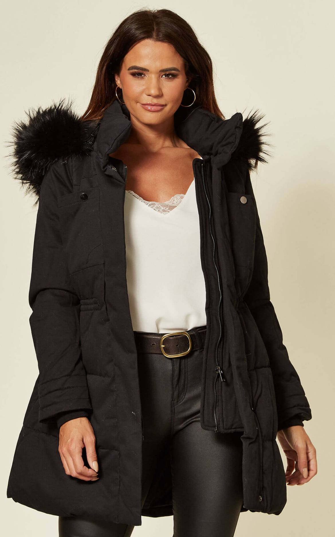 Model wears black parka over white t-shirt and jeans