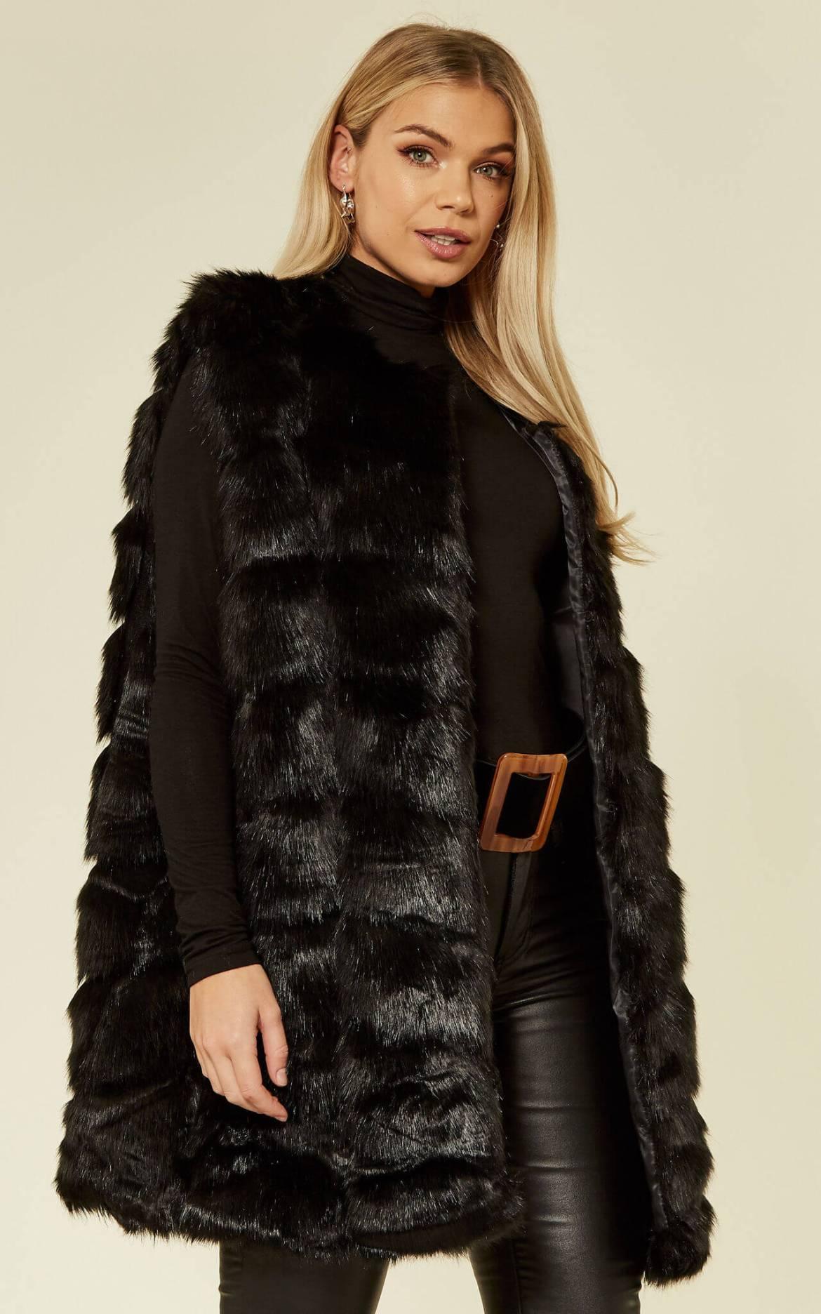 Model wears the black faux fur gilet over black rollneck