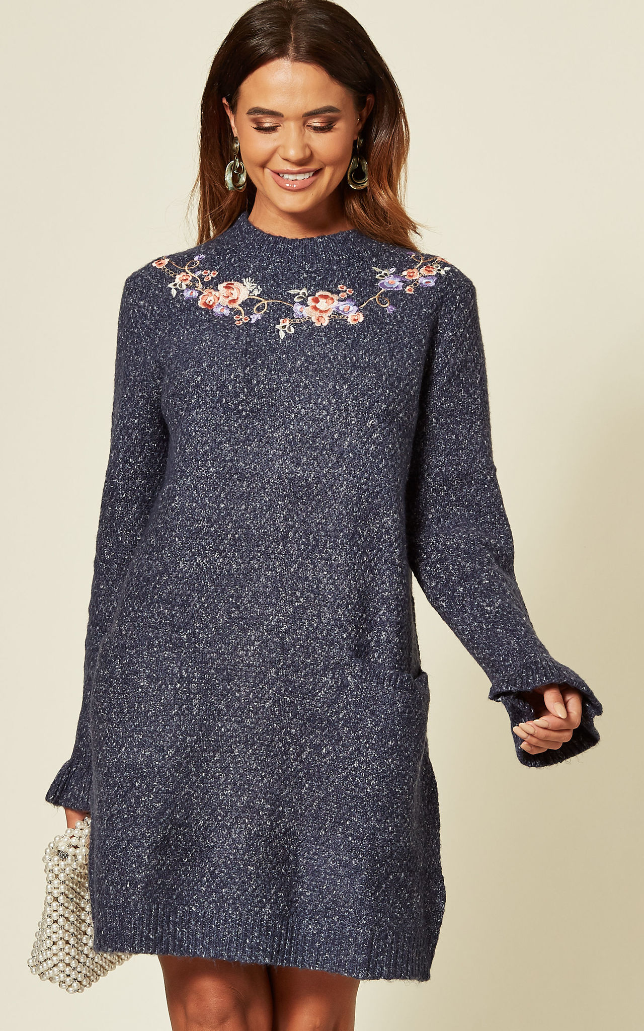 Model wears a knitted tunic dress in light blue with floral embroidery