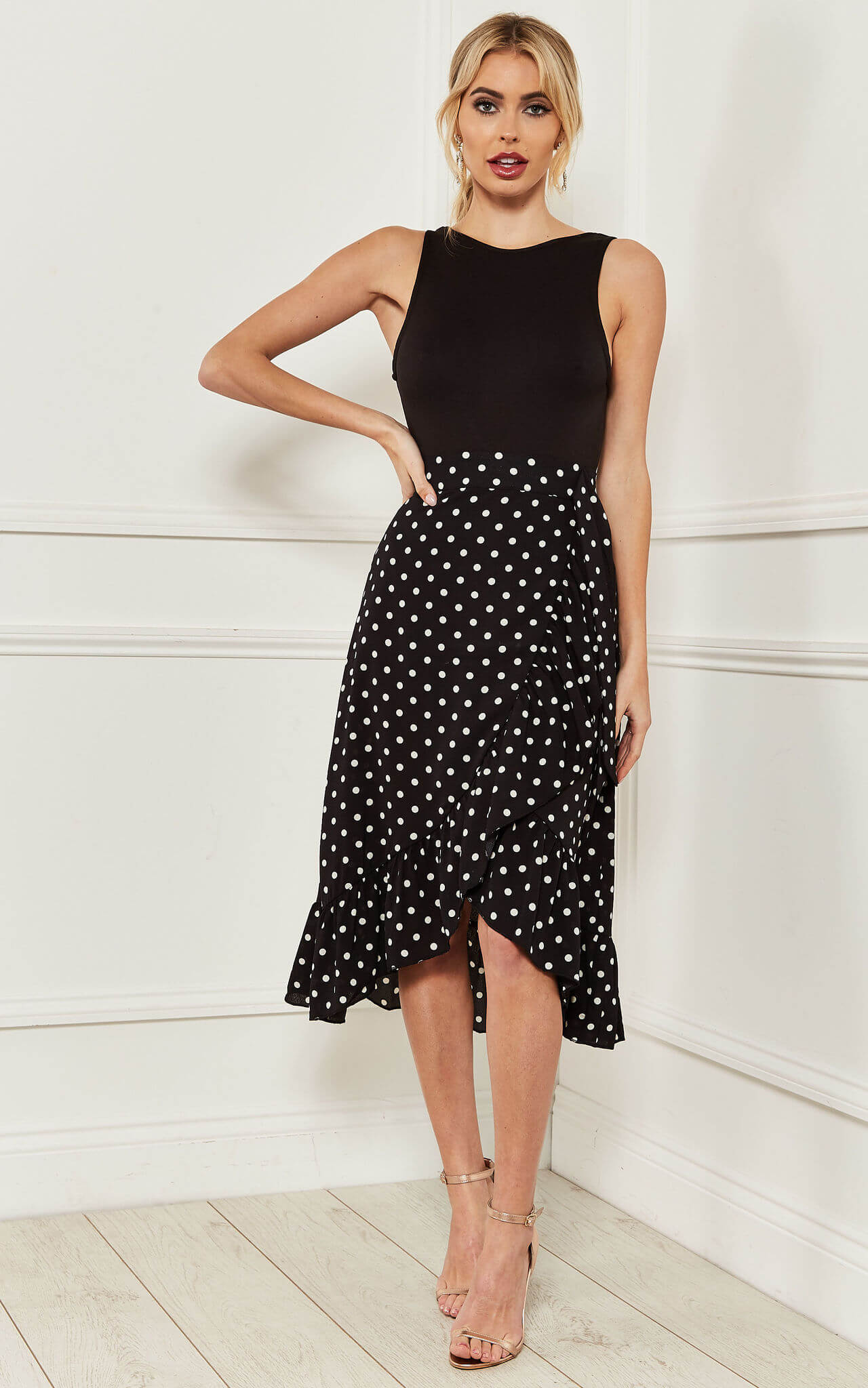 Model wears a black ruffle wrap midi skirt with white polka dots with a black top