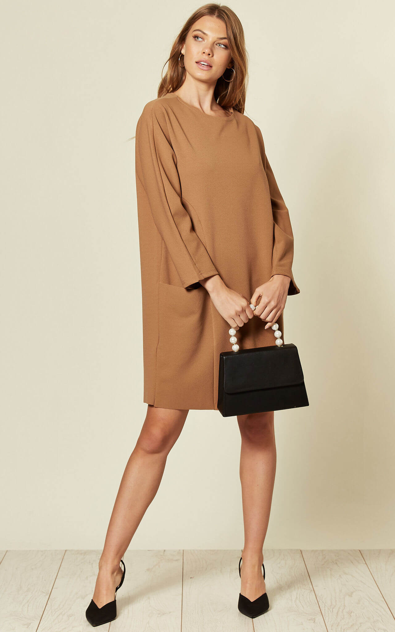 Model wears a long sleeve tunic dress in camel with pockets and a black handbag
