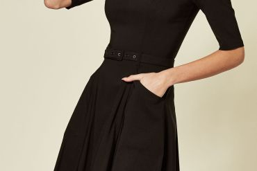 Model wears a black midi skater dress with white peter pan collar with pockets