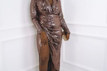 Model wears rose gold wrap midi dress with v neck and strappy heels
