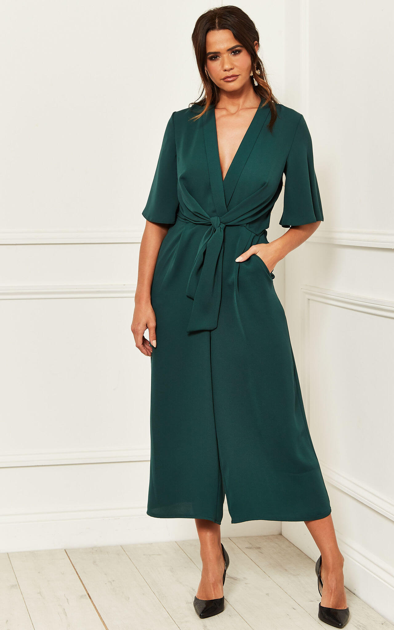 Model wears a green kimono culotte jumpsuit with a knot tie front and black heels