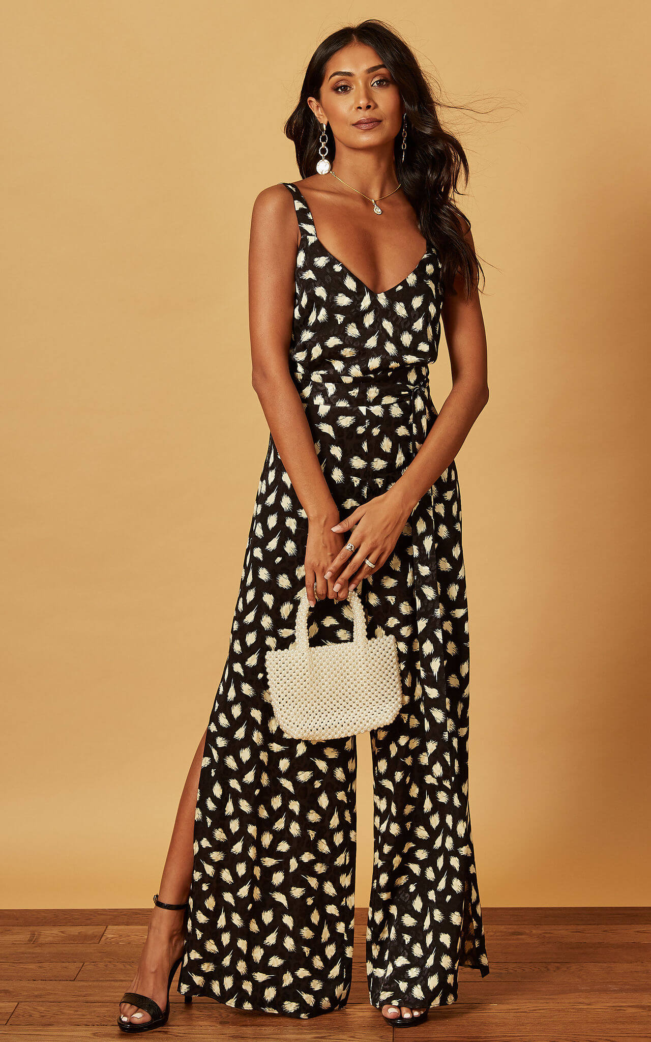 Model wears strappy leopard jumpsuit with leaf print and pearl bucket bag and black heels