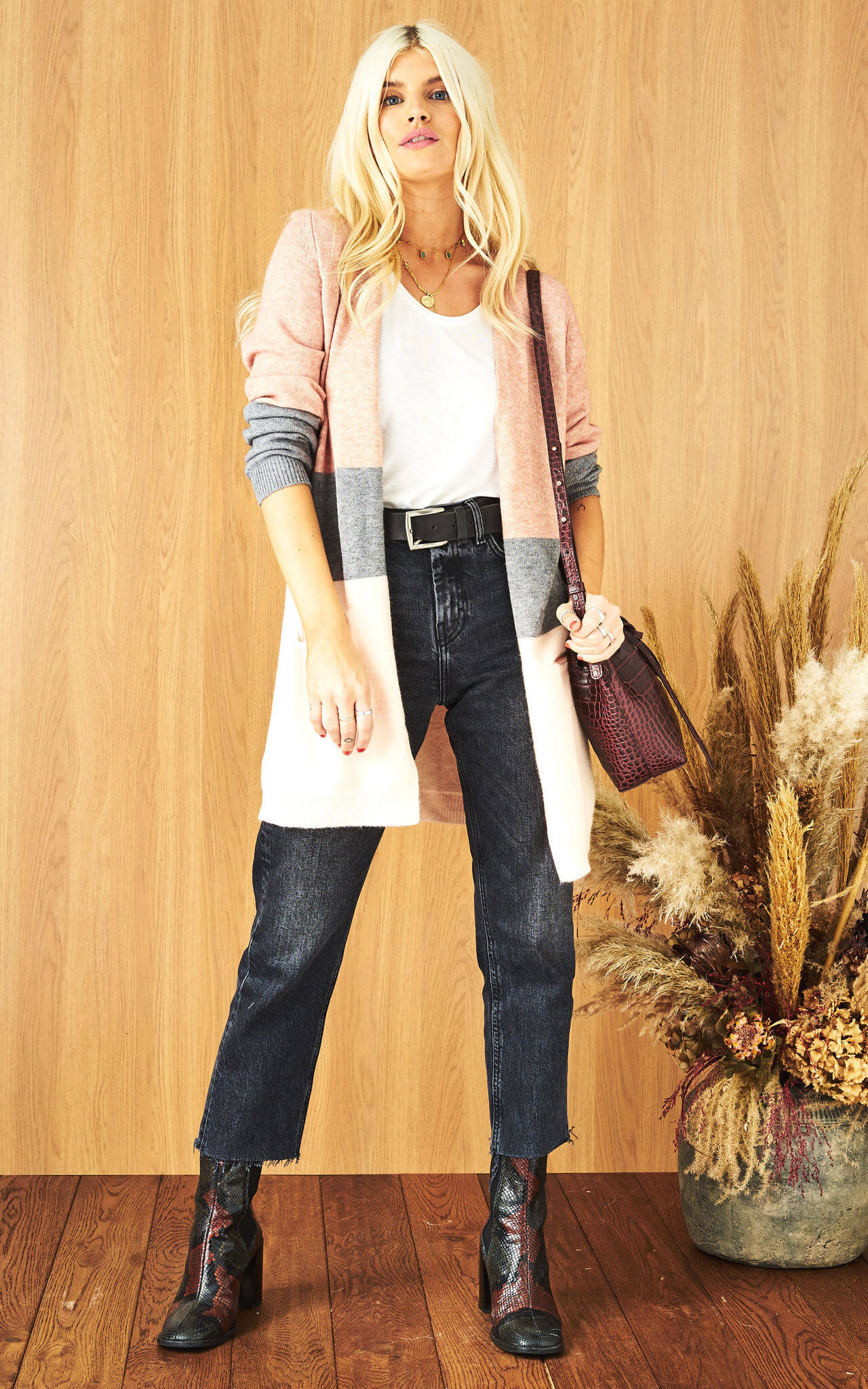 Model wears leather jeans and a white t-shirt with a pink and grey stripe open front cardigan