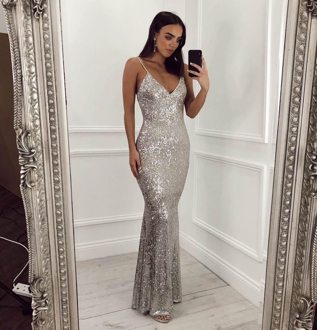 Model wears a floor length silver sequin dress in a mirror selfie