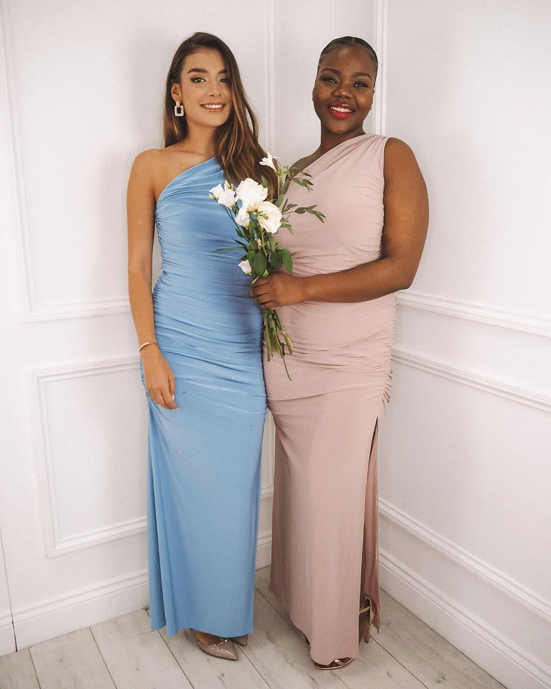 Two models wear the same one shoulder ruched maxi dress, one wearing blue and the other in light grey
