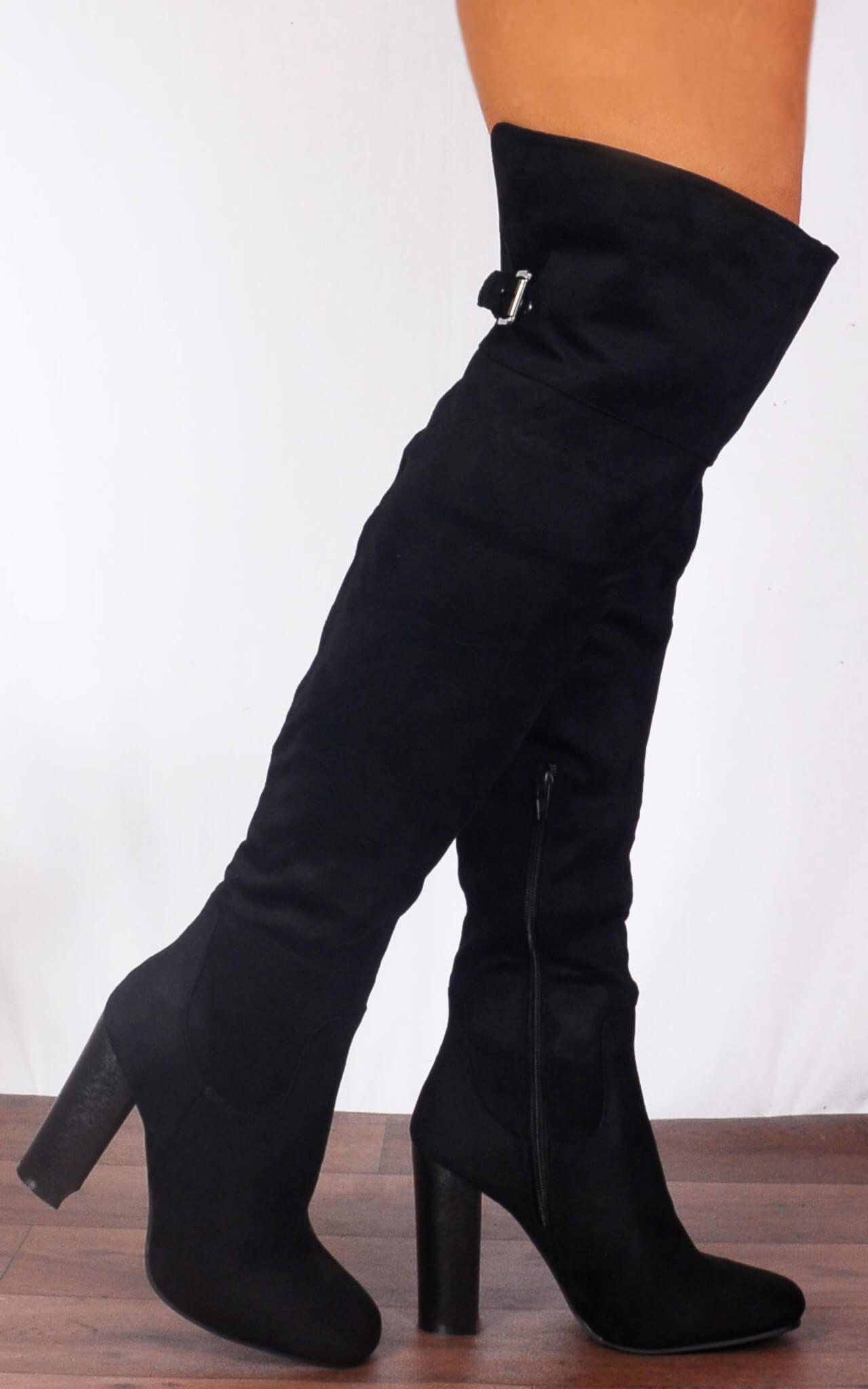 Model wears a black over the knee boot with buckle