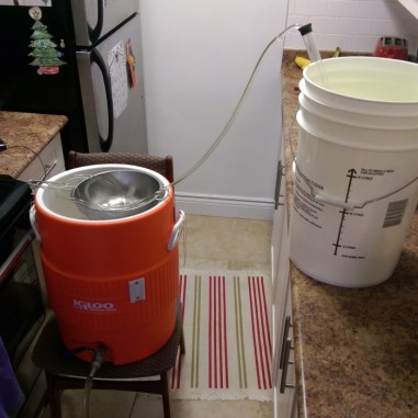 Hot water from the white pail flows through tube to colander to rinse grain of sugars.