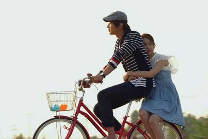 Boong-Do and Hee-Jin ride a bicycle