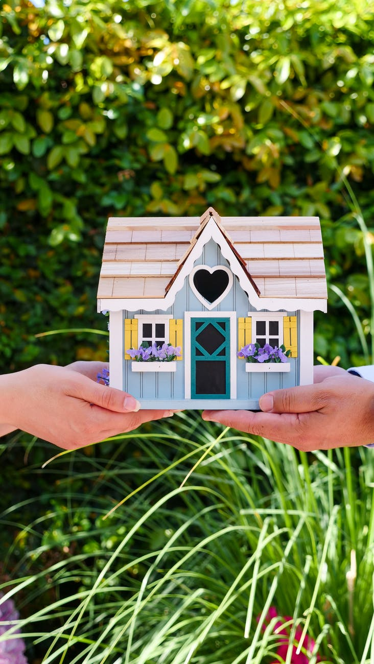people holding a miniature wooden house