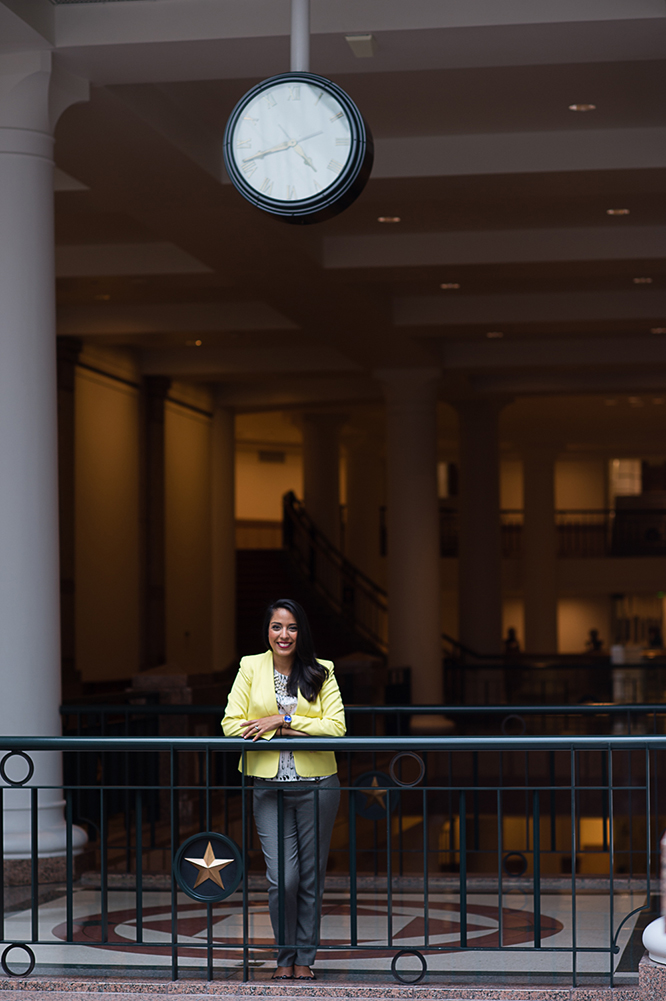 Mari in a yellow jacket smiling at the railings near the gift shop the Texas State Capitol