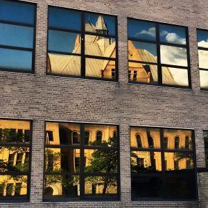 Wayne State University's Old Main reflected in the glass of a newer university building.