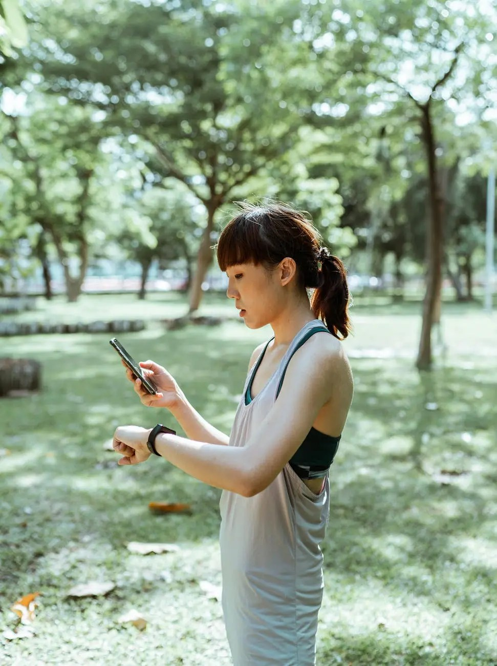 slim asian woman using smart watch and smartphone in park