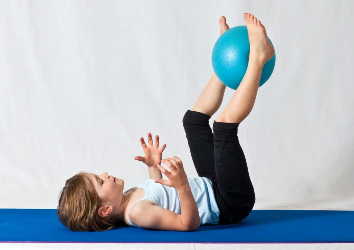 girl in white shirt and black pants lying on blue exercise ball