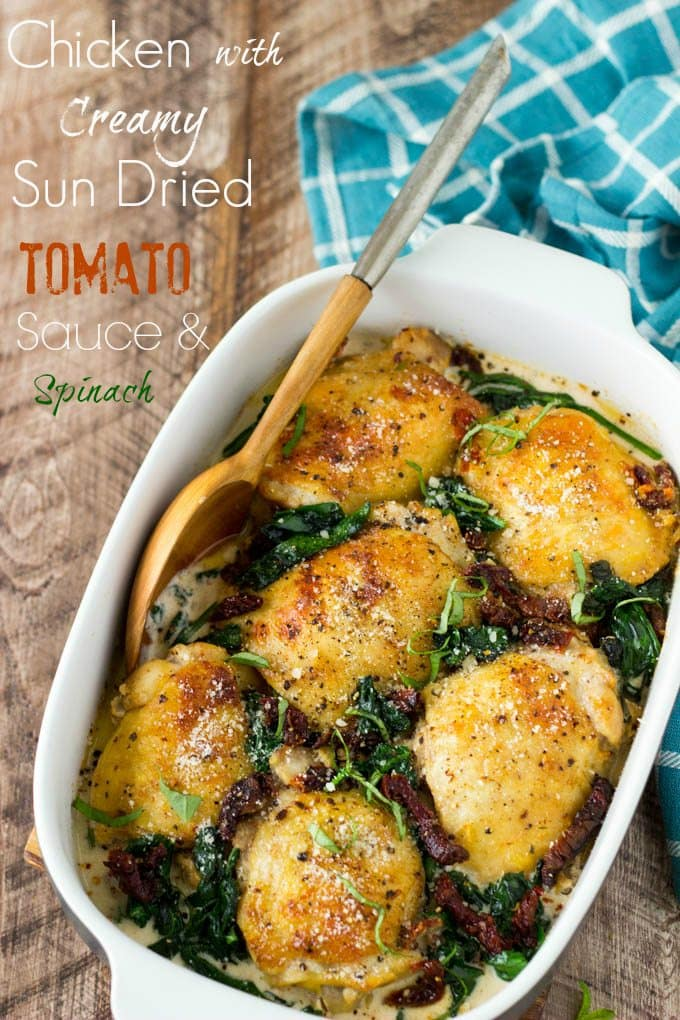 """Chicken with Creamy Sun Dried Tomato Sauce + Spinach- Super Easy! Chicken thighs are smothered in a """"to die for""""creamy Sun Dried Tomato and Parmesan sauce and baked to golden brown perfection. It's easy, it's comforting, and it's only about 330 calories per serving."""