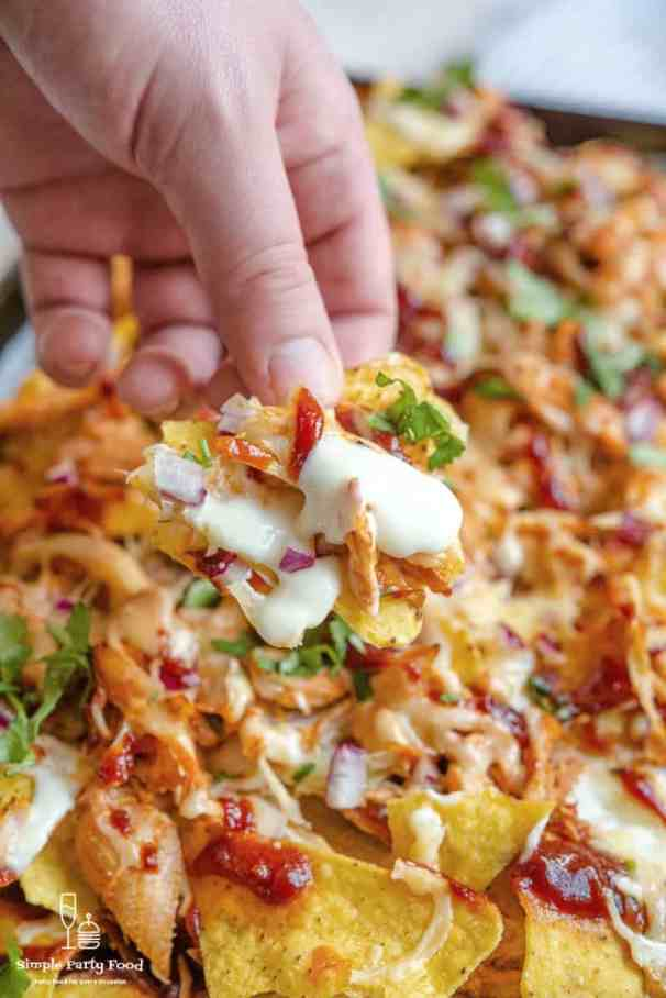 SIMPLE Loaded Sheetpan BBQ Chicken Nachos - rotisserie chicken, red onion, 3 different cheeses, bbq and tortilla chips make an epic appetizer #simplepartyfood