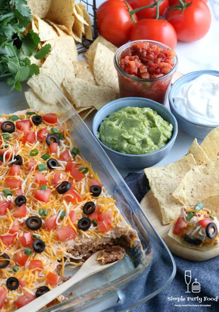 SIMPLE Layered Taco Dip - ground beef, beans, cream cheese, sour cream and toppings make the most delicious dip for any party! #tacodip #partyfood #appetizers #simplepartyfood