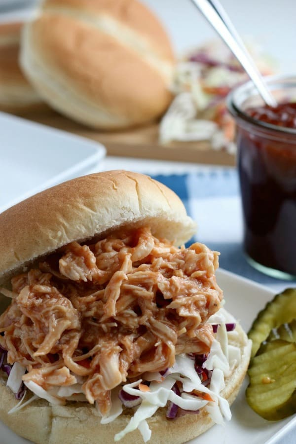 SIMPLE Slow Cooker Pulled BBQ Chicken - super easy to make without making the kitchen hot, feeds a crowd. Perfect summer dinner #pulledchicken #bbqchicken #summerdinners #slowcooker #slowcookerchicken #simplepartyfood
