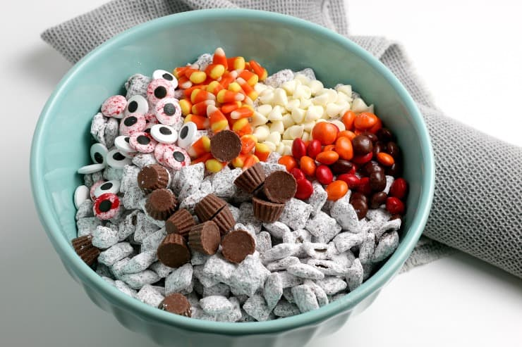 Halloween Puppy Chow in a bowl with candy corn, edible eyes, Reeses pieces