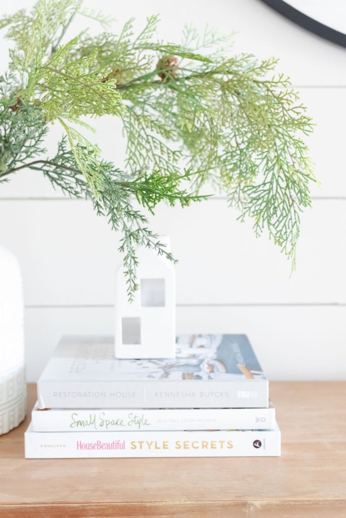 cedar greenery styled with stacked book for a simple and clean entryway.