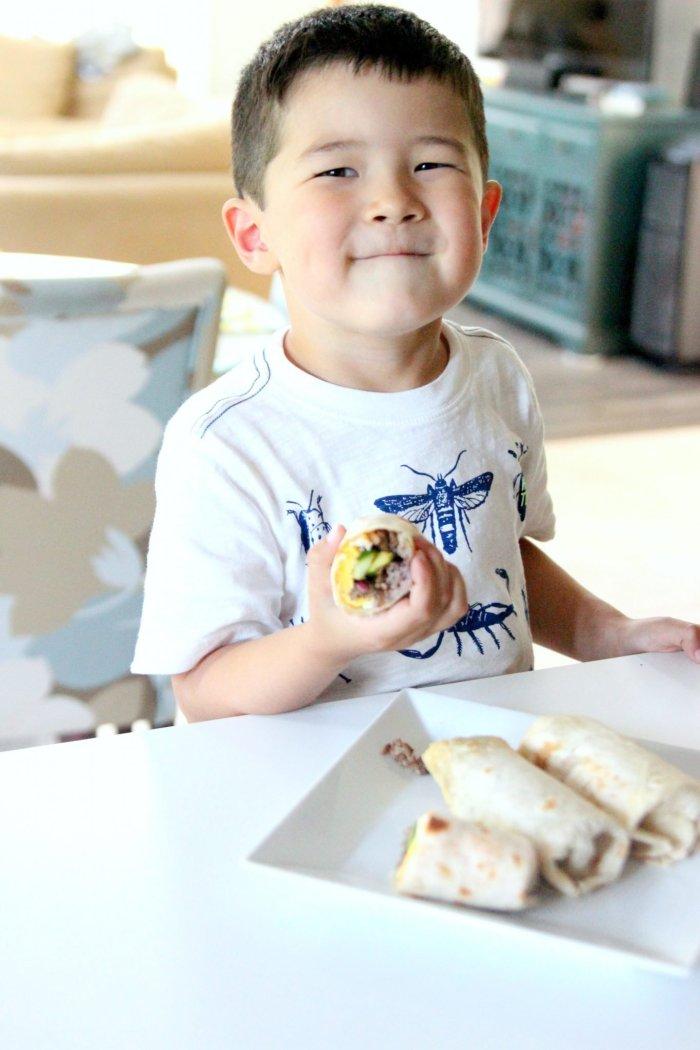 a kid holding a burrito