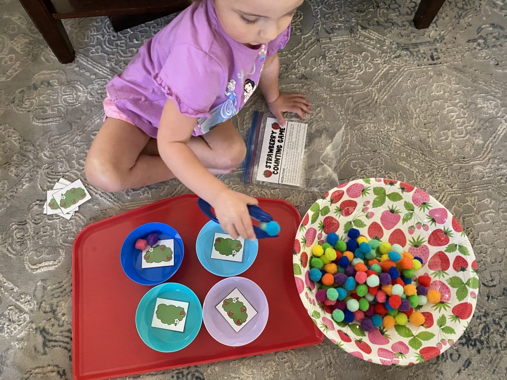 Caroline playing strawberry counting game on carpet with tweezers